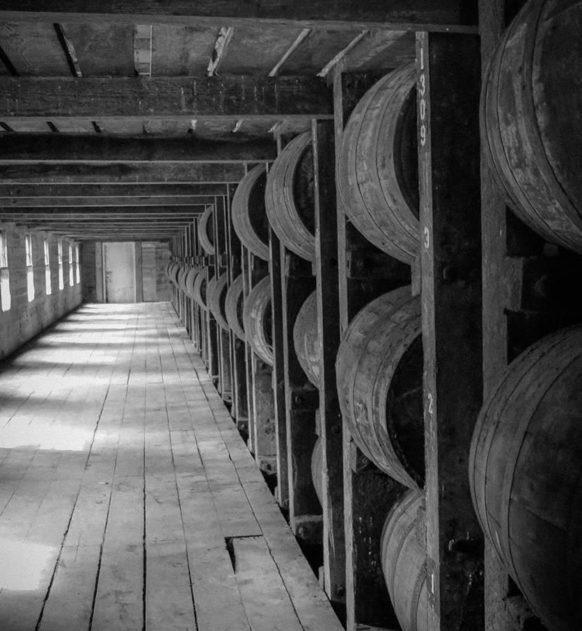 Dusty whiskey barrels in storage